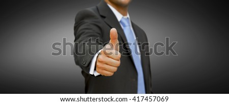 Businessman at the office with his thumb up