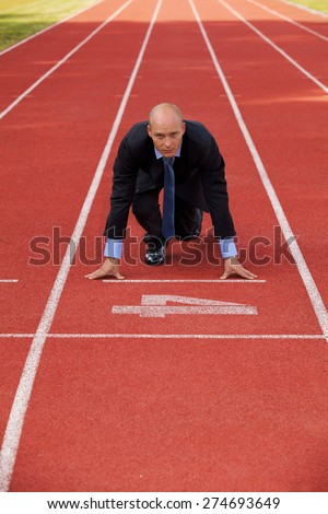 Businessman at the start line of running track - stock photo