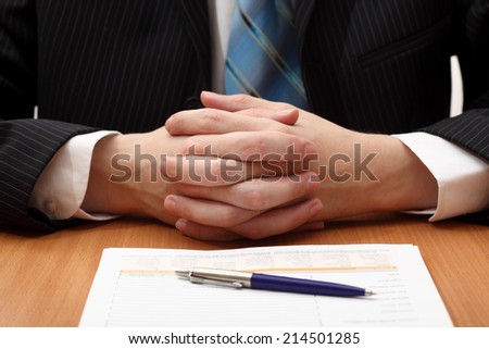 Businessman at work. Businessman sitting at a desk with documents or contract or application form. Closeup.