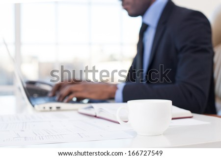 Businessman at work. Close-up of African businessman using computer with a coffee cup on the foreground - stock photo