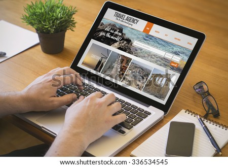 Businessman at work. Close-up top view of man working on laptop withtravel agency website on screene. all screen graphics are made up. - stock photo