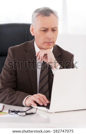 Businessman at work. Confident senior man in formalwear working on laptop while sitting at his working place