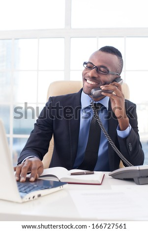 Businessman at work. Confident young African businessman in glasses talking on the mobile phone and using computer while sitting at his working place - stock photo