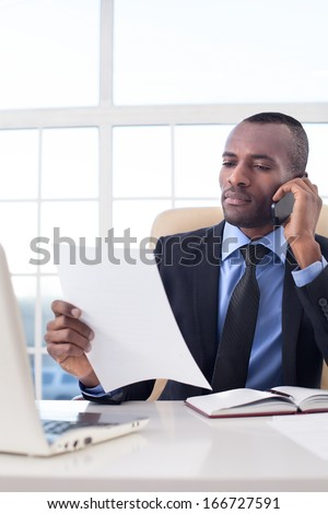 Businessman at work. Confident young African businessman talking on the mobile phone and checking documents while sitting at his working place - stock photo