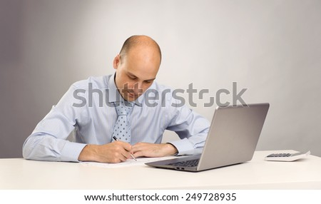 Businessman at work. Handsome young man in shirt and tie working on laptop while sitting at his working place