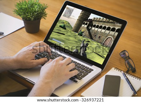 Businessman at work procrastinating. Close-up top view of man working on laptop with videogame. all screen graphics are made up. - stock photo