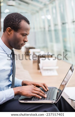 Businessman at work. Side view of young and confident African man in formalwear working on laptop while sitting at his working place - stock photo