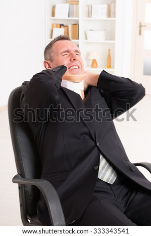 Businessman at work wearing neck brace