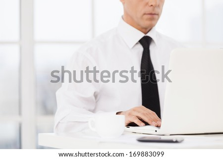 Businessman at working place. Cropped image of man in shirt and tie using computer while sitting at his working place