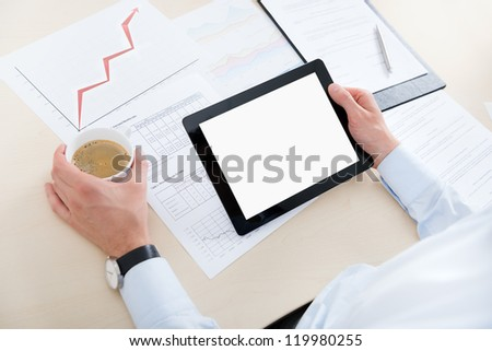 Businessman at workplace drinking coffee and looking at the blank digital computer. - stock photo