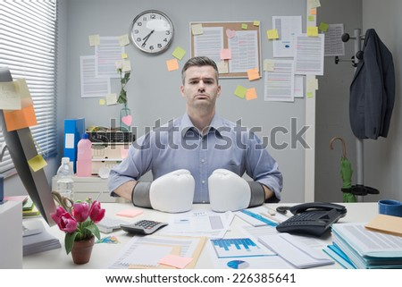 Businessman at workplace wearing boxing gloves with fists on desktop and confident expression. - stock photo