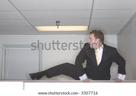 Businessman attempts to climb over his cubicle trying to escape out of his office while wearing a black suit - stock photo