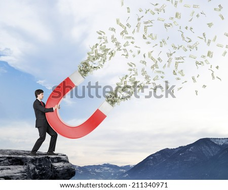 Businessman attracts money with a large red magnet.  - stock photo
