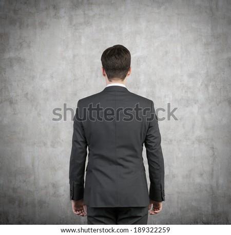 Businessman, back. Concrete wall. - stock photo