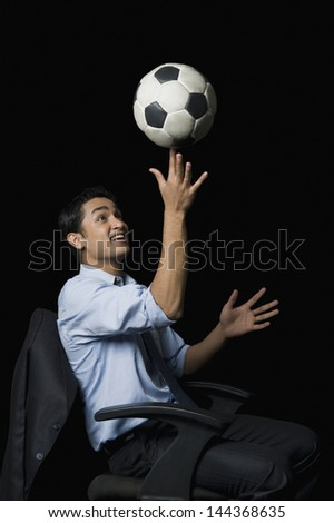 Businessman balancing a soccer ball on his finger - stock photo