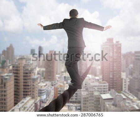 Businessman balancing on a wire with sky clouds cityscape background. - stock photo
