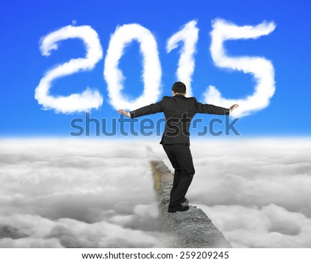 Businessman balancing on concrete ridge with white 2015 year shape cloud and blue sky cloudscape background