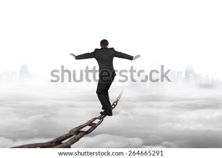 Businessman balancing on old iron chain with cloudy sky cityscape skyline background - stock photo
