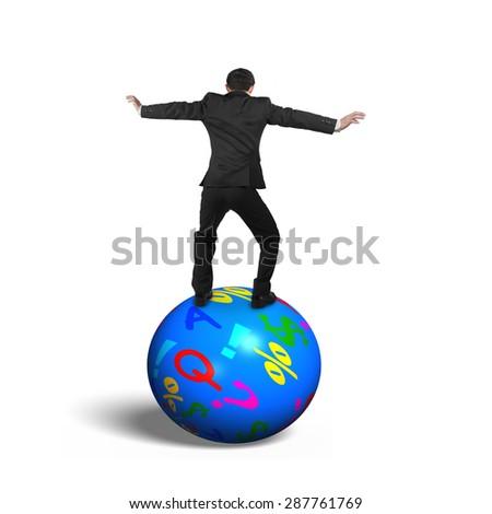 Businessman balancing on the colorful symbols ball, isolated on white background. - stock photo