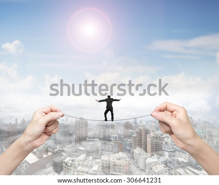 Businessman balancing on tightrope with woman two hands holding two sides, on sunny sky cityscape background. - stock photo