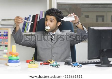 Businessman behaving like a kid in an office - stock photo