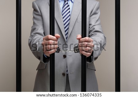 Businessman behind bars in prison concept for white collar crime - stock photo