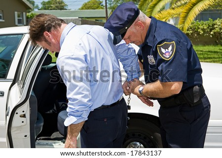 Businessman being handcuffed and placed under arrest. - stock photo