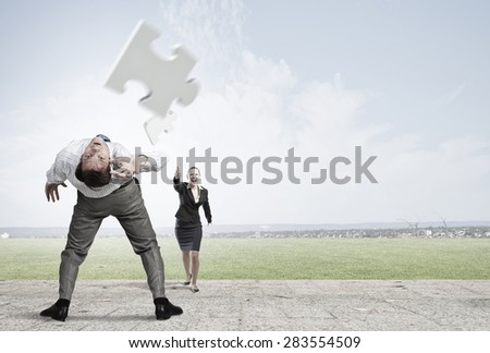 Businessman bent over and evading from flying puzzle element - stock photo