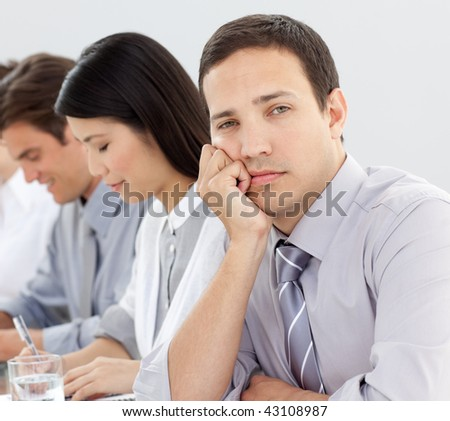 Businessman bored at a presentation with his team - stock photo