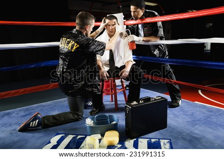 Businessman Boxer Being Treated Between Rounds - stock photo