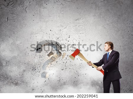 Businessman breaking stone question mark with axe - stock photo