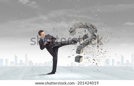 Businessman breaking stone question mark with karate kick - stock photo