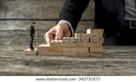 Businessman building a staircase of wooden pegs for another entrepreneur to climb up the ladder of success. - stock photo