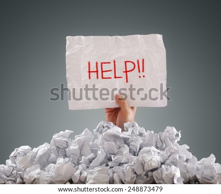 Businessman buried under crumpled pile of papers with a help sign - stock photo