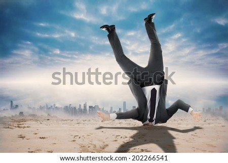 Businessman burying his head against dusty path leading to city under the clouds - stock photo