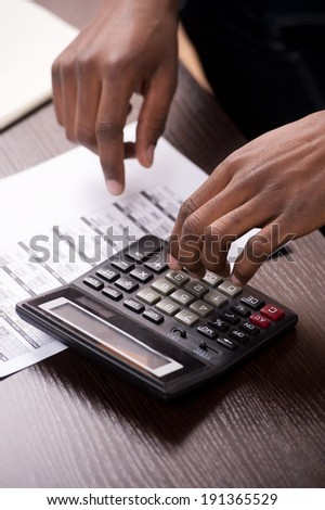 Businessman Calculating Bills. Cropped shot of a businessman calculating bills on a wooden table.  - stock photo