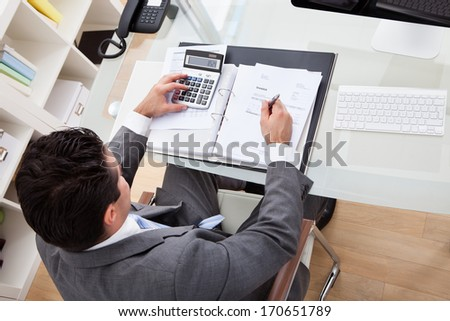 Businessman Calculating Documents Using Calculator In Office - stock photo