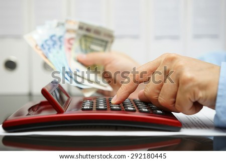 businessman calculating profit, holding cash in hand - stock photo