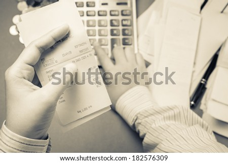 Businessman calculating receipts in hand - stock photo