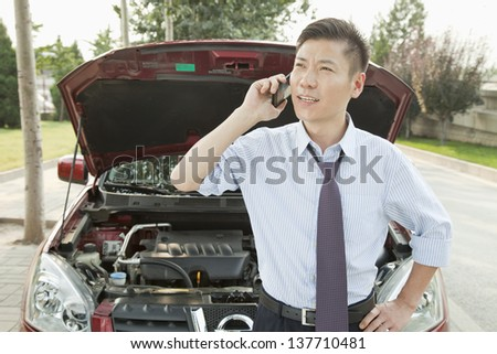 Businessman Calling for Roadside Assistance - stock photo