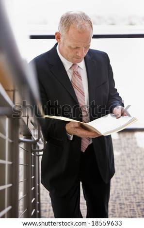 Businessman carefully reading paperwork near office stairs