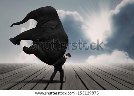Businessman carry elephant by himself under blue sky as leadership concept  - stock photo