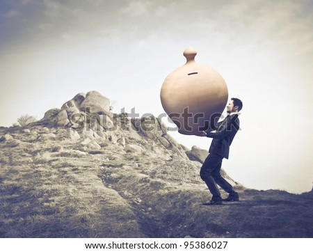 Businessman carrying a giant money box on a rock - stock photo