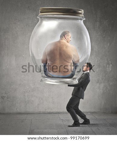 Businessman carrying a jar with an obese man in it - stock photo