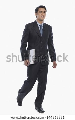 Businessman carrying a laptop - stock photo