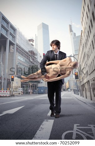 Businessman carrying a mannequin on a city street