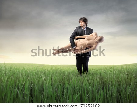 Businessman carrying a mannequin on a green meadow