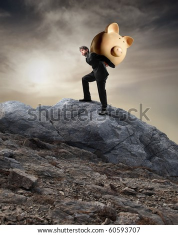 Businessman carrying a money box on his shoulders and climbing a rock - stock photo
