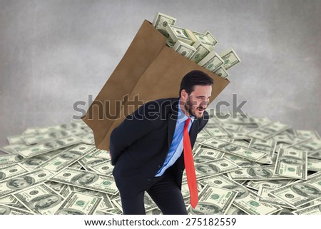 Businessman carrying bag of dollars against grey room