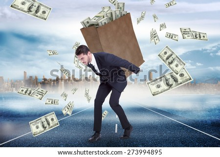 Businessman carrying bag of dollars against large city on the horizon - stock photo